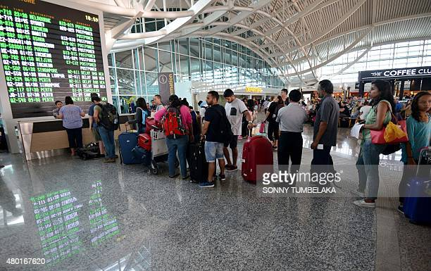 Passengers queue up at the international terminal at Bali's Ngurah Rai airport in Denpasar for information of flight delays due to volcanic ash near...