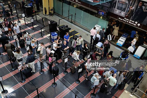Passengers queue up outside a Transportation Security Administration checkpoint at Ronald Reagan National Airport May 27, 2016 in Arlington, VA....