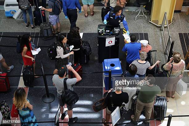 Passengers queue up outside a Transportation Security Administration checkpoint at Ronald Reagan National Airport May 27 2016 in Arlington VA...