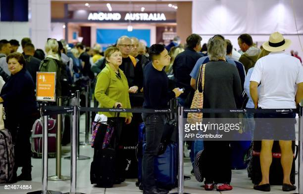 Passengers queue up to check in at the international terminal in Sydney Airport on July 31 2017 Four men accused of plotting to bring down a plane...