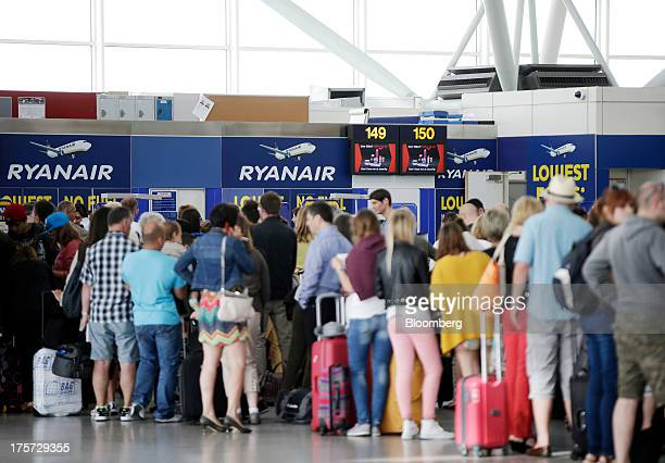 Passengers queue with their luggage for a flight with budget airline Ryanair Holdings Plc at Stansted Airport operated by Manchester Airports Group...