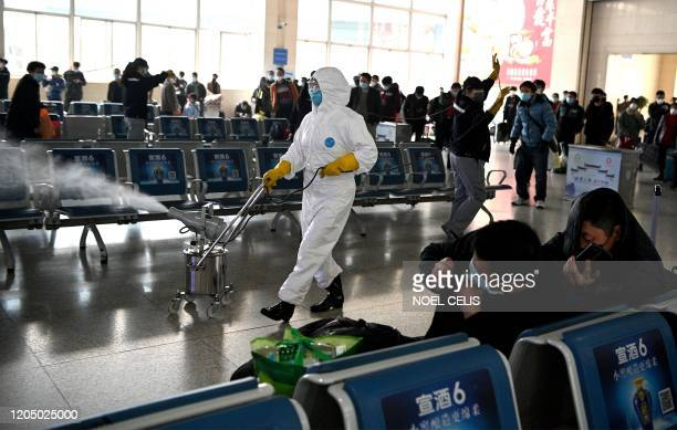 Passengers react as a worker wearing a protective suit disinfects the departure area of the railway station in Hefei, Chinas eastern Anhui province...