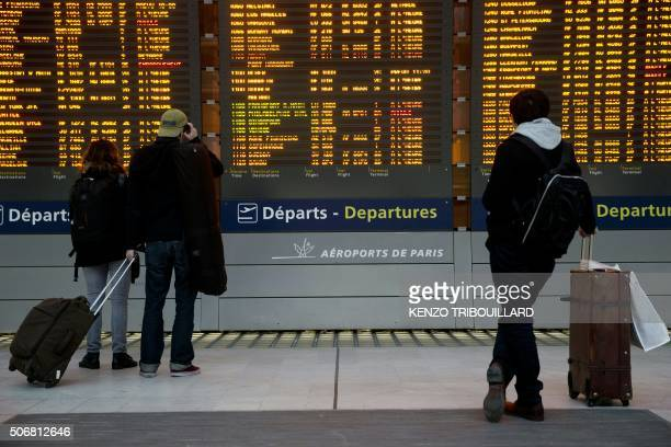 Passengers read a departure board on January 26 2016 at Roissy CharlesdeGaulle airport during a nationwide strike to protest against job cuts The...