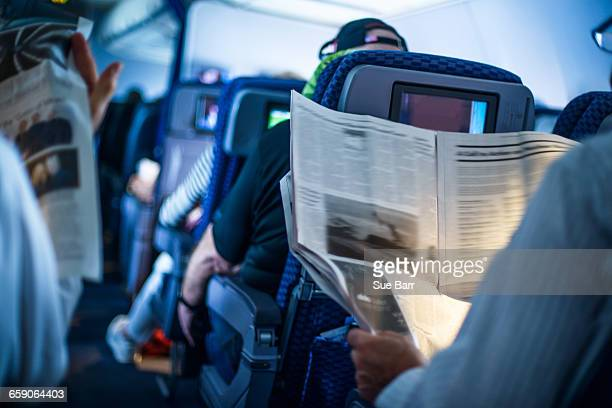 Passengers reading newspapers on board flight