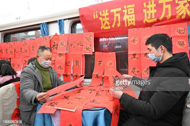 Passengers receive Spring Festival Couplets as gifts onboard a train ahead of the Chinese New Year, the Year of the Ox, on February 3, 2021 in...