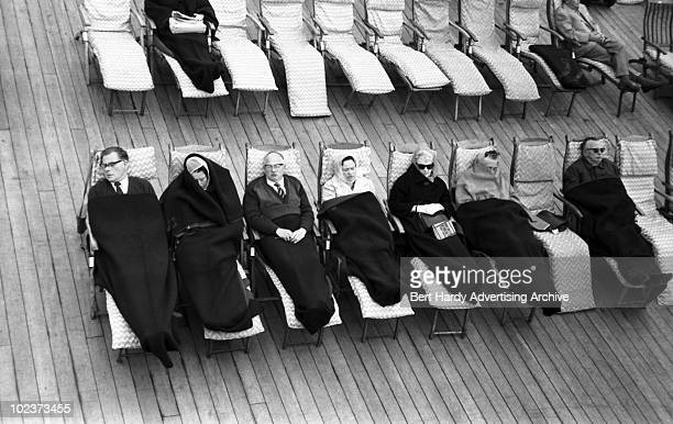 Passengers relaxing on the deck of the Cunard liner 'Queen Elizabeth' as she makes her way from Southampton to New York May 1964