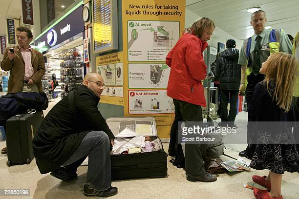 Passengers repack their bags to comply with new security procedures as they prepare to go through security at terminal 1 of Heathrow Airport on...