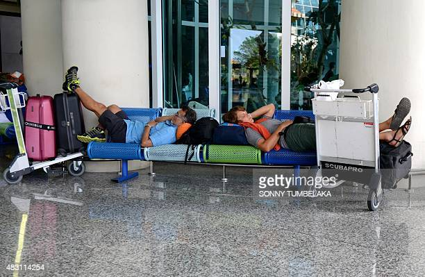 Passengers rest after flights were delayed at Bali's Ngurah Airport in Denpasar on August 6 2015 Indonesian authorities ordered a fresh shutdown of...
