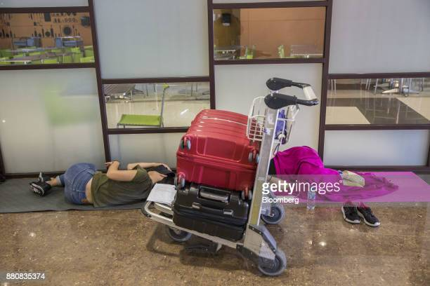 Passengers rest on the floor next to their luggage at Ngurah Rai International Airport near Denpasar Bali Indonesia on Tuesday Nov 28 2017 The...