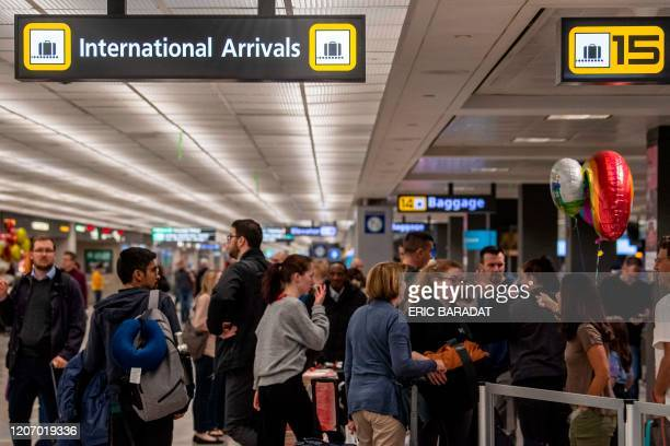 Passengers reunite with family members in the International arrivals zone at Dulles airport outside Washington on March 13 2020 US President Donald...