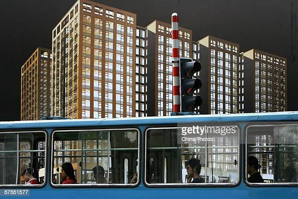 Passengers ride a bus past a giant real estate billboard on May 2 2006 in Nanjing of Jiangsu Province China Housing prices in 70 large and medium...