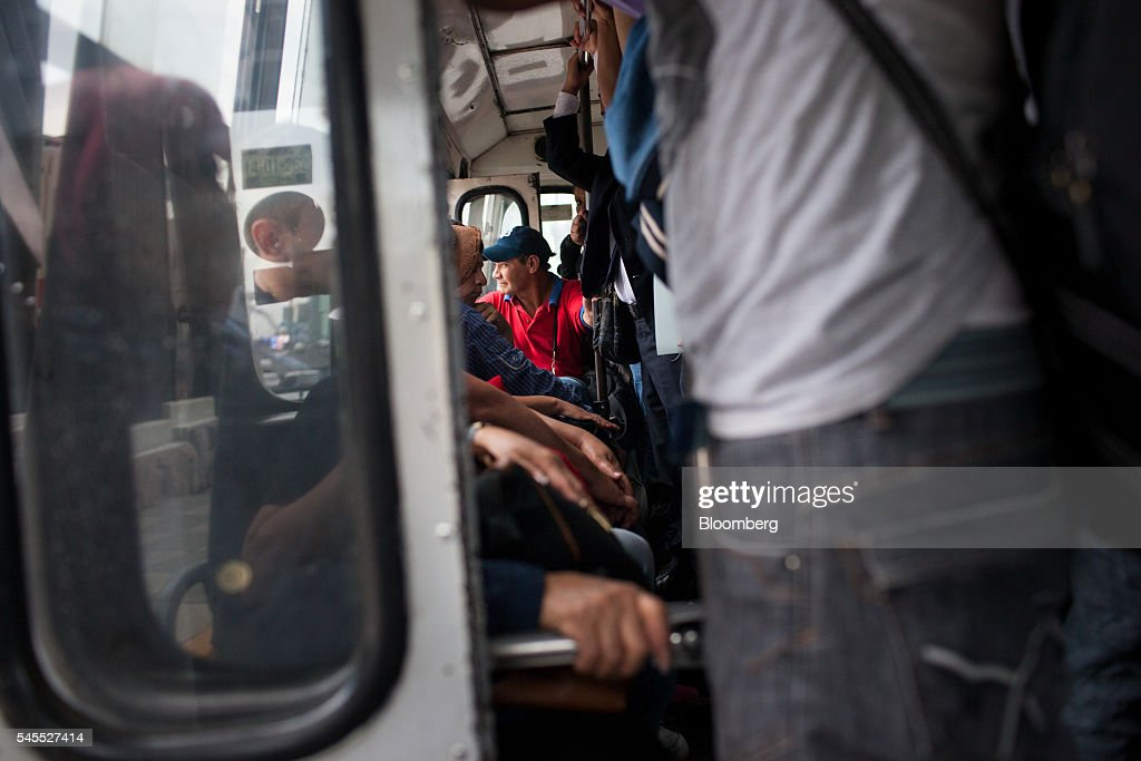 Passengers ride a micro bus in Mexico City, Mexico, on Tuesday, June 28, 2016. The air quality in Mexico City has risen above the government's acceptable limits triggering restrictions on automobile usage and stricter vehicle emissions testing. Photographer: Brett Gundlock/Bloomberg via Getty Images