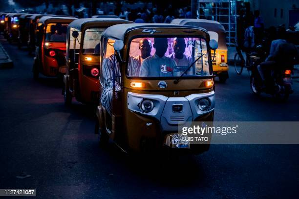 Passengers ride a tuk tuk during sunset in a traffic jam created by All Progressives Congress Party supporters celebrating initial results released...
