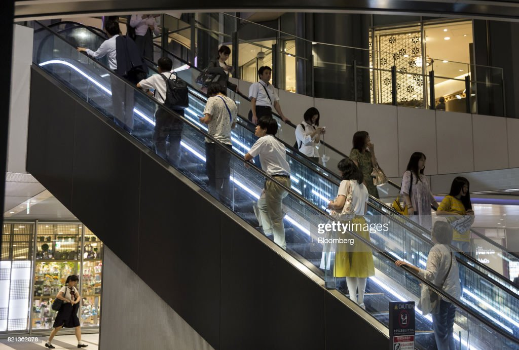 Passengers ride escalators at Shibuya Station in Tokyo, Japan, on Tuesday, July 18, 2017. July 24 marks the first dry run of a 'Telework Day' encouraging people to work from home as the city gears up to host the 2020 Summer Olympics. Authorities are seeking ways to make room for 920,000 spectatorsexpected to visit Tokyo each day during the games. Photographer: Tomohiro Ohsumi/Bloomberg via Getty Images