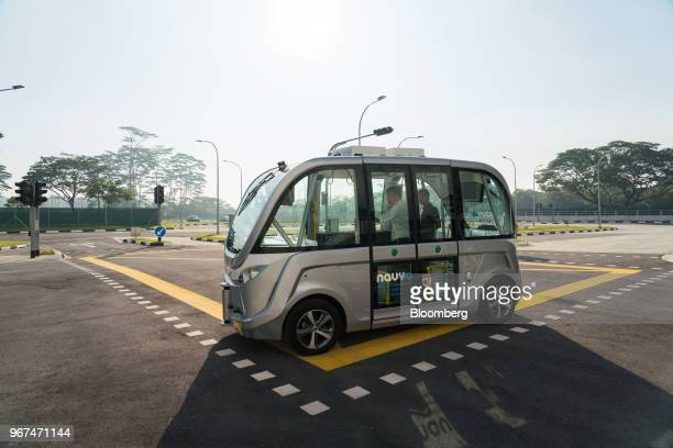 Passengers ride in a Navya SAS autonomous electric passenger bus travelling along the test circuit at the Centre of Excellence for Testing Research...