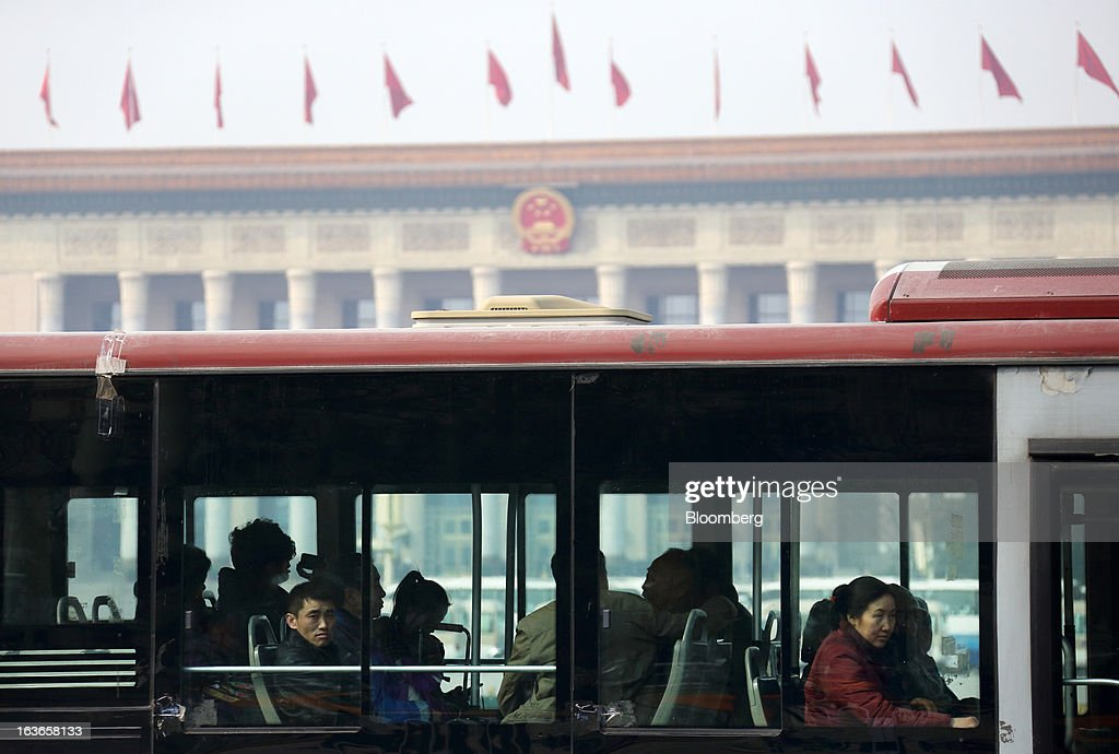 Passengers ride on a bus in front of the Great Hall of the People in Beijing, China, on Thursday, March 14, 2013. Xi Jinping was named China's president by the national legislature, replacing Hu Jintao in the country's most rapid formal transfer of power in more than a generation. Photographer: Tomohiro Ohsumi/Bloomberg via Getty Images