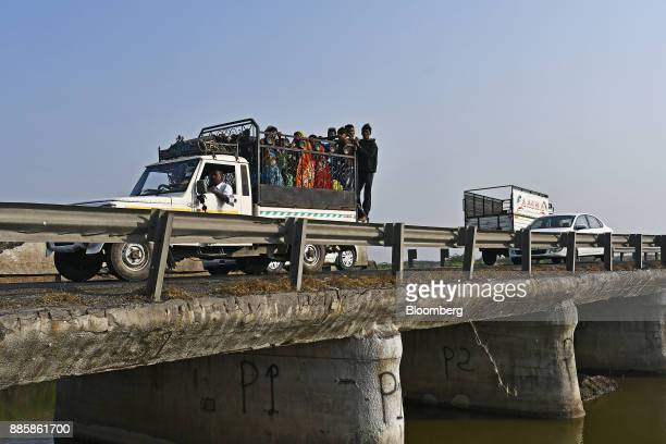 Passengers ride on the back of a pick up truck travelling over a bridge on a project site for a 920squarekilometer industrial area located on the...