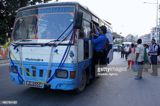 Passengers ride on top of overcrowded public bus as limited public transportation operates due to an ongoing fuel crisis in Kathmandu Nepal on...