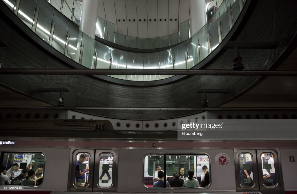 Passengers riding a train on the Toyoko line, operated by Tokyu Corp., wait at Shibuya Station in Tokyo, Japan, on Tuesday, July 18, 2017. July 24 marks the first dry run of a 'Telework Day' encouraging people to work from home as the city gears up to host the 2020 Summer Olympics. Authorities are seeking ways to make room for 920,000 spectatorsexpected to visit Tokyo each day during the games. Photographer: Tomohiro Ohsumi/Bloomberg via Getty Images