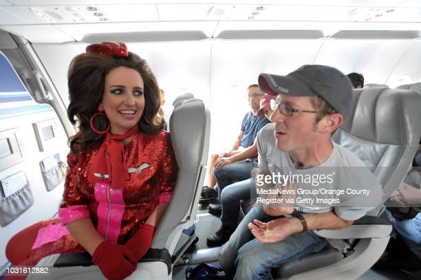 USA Passengers Ryan Swedlund chats with comedian and 'air hostess' Pam Ann pour champaign during JetBlue's JetPride flight 1969 from San Francisco to...