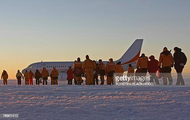 Passengers scientists government officials and ground crew walk on the purposebuilt Wilkins glacial blue ice runway to the first Airbus A319 jet to...