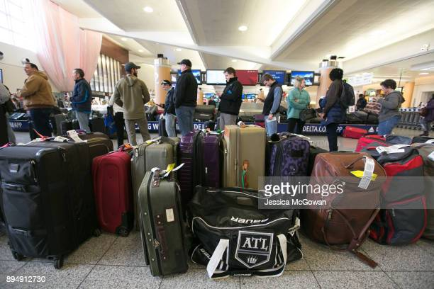 Passengers search for their luggage near rows of unclaimed baggage at HartsfieldJackson Atlanta International Airport on December 18 2017 in Atlanta...