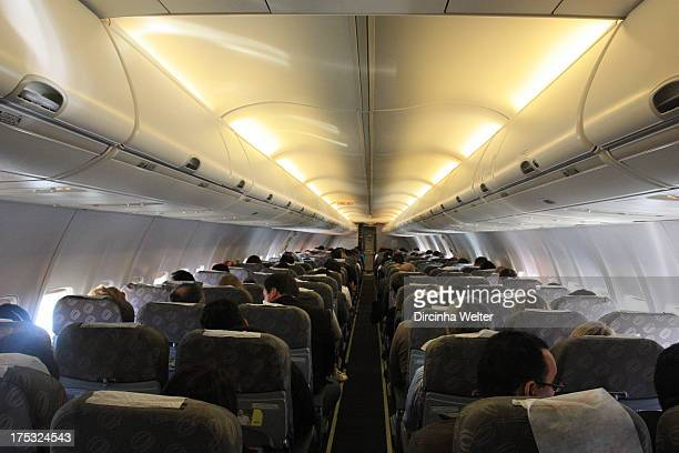 Passengers seated inside the plane waiting for takeoff. Passageiros sentados dentro do avião aguardando a decolagem.