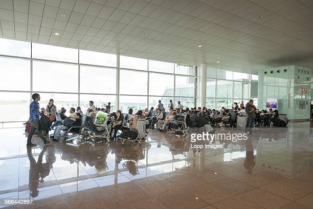 Passengers seated waiting at Barcelona airport departure gate