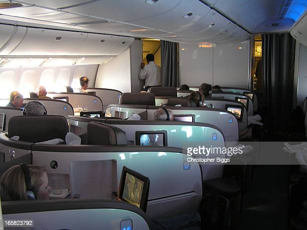 Passengers settled into an Air New Zealand Business Class Cabin for a cross Pacific flight. It has angled flat beds with a footrest each on the aisle...