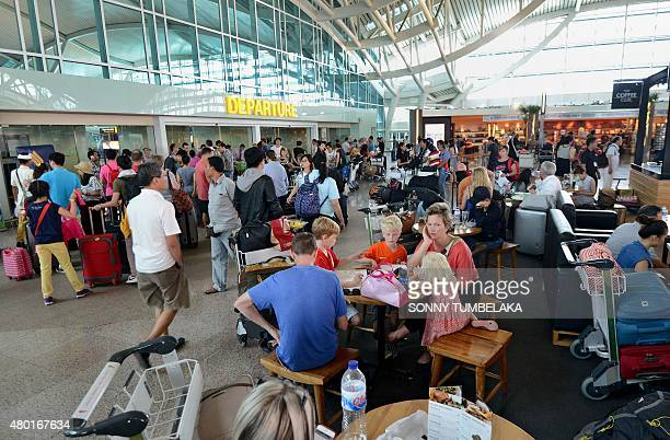 Passengers sit around the international terminal at Bali's Ngurah Rai airport in Denpasar waiting for information of flight delays due to volcanic...