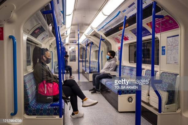 Passengers sit in a quiet London Underground tube train in London on May 14, 2020 after a partial loosening of the coronavirus lockdown guidelines. -...