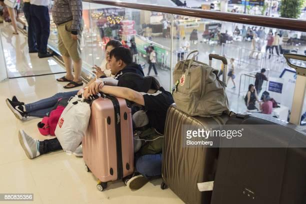 Passengers sit next to their luggage at Ngurah Rai International Airport near Denpasar Bali Indonesia on Tuesday Nov 28 2017 The airport inBaliwill...
