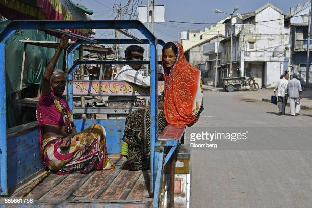 Passengers sit on an auto rickshaw in the village of Dholera near a project site for a 920squarekilometer industrial area located on the DelhiMumbai...