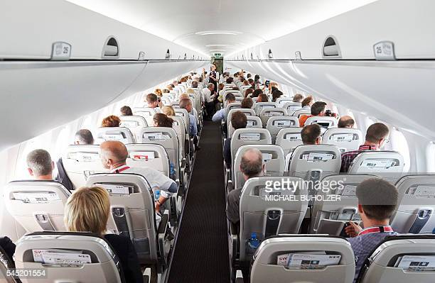 Passengers sit on July 6 2016 aboard the Swiss International Air Lines' new Bombardier CS 100 passenger jetliner during a flight over the Swiss Alps...