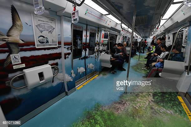 Passengers sit on wetlandthemed carriage of Fuzhou Metro line 1 on January 6 2017 in Fuzhou Fujian Province of China Carriages themed on wetland...