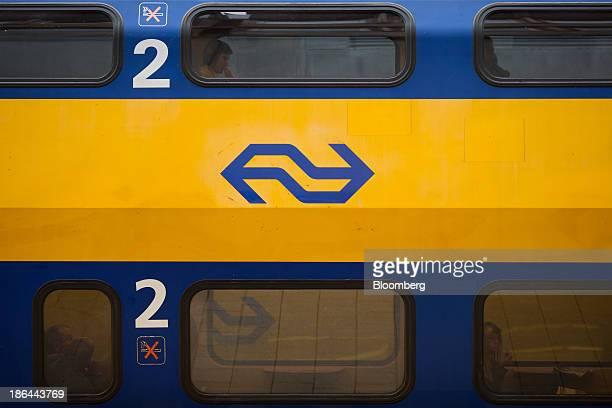 Passengers sit onboard a DubbeldeksInterregiomaterieel passenger train operated by Nederlandse Spoorwegen the principal passenger railway operator in...