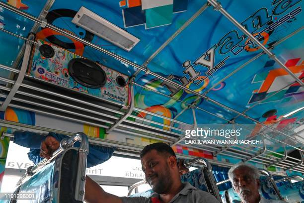 Passengers sit under a speaker in a private bus in Piliyandala a suburb of Colombo on January 2 2020 Sri Lanka's government on January 2 gave bus...