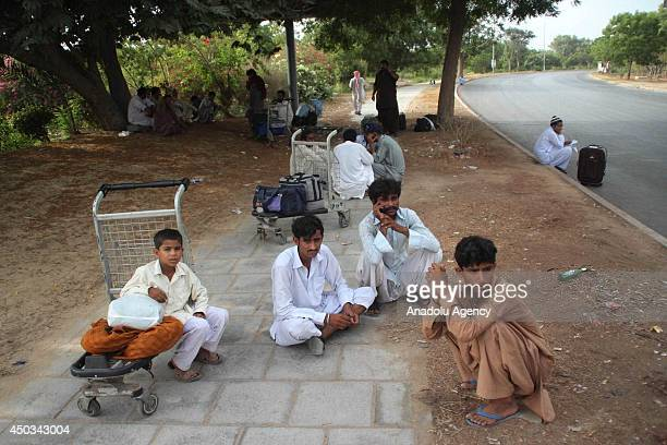 Passengers sits outside the Jinnah International Airport waiting for departure signal from the officials in Karachi Pakistan on June 9 2014 in...