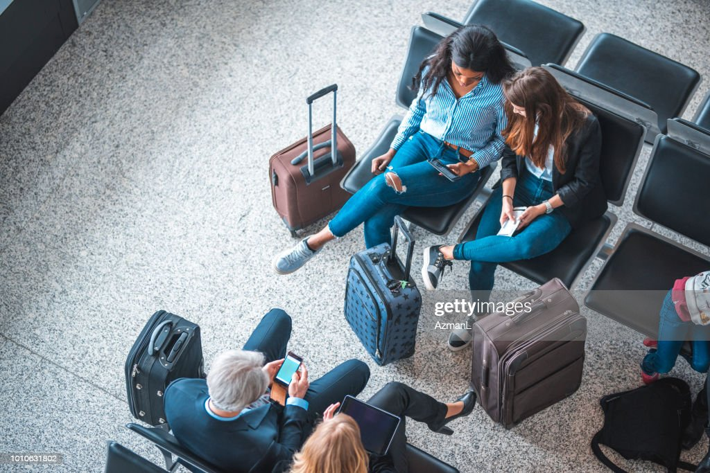 Passengers sitting on seats in departure area : Stock Photo