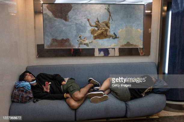 Passengers sleep on a couch of the lounge of a passenger ship sailing from Greece to Italy on August 7, 2020 at sea between Italy and Greece....