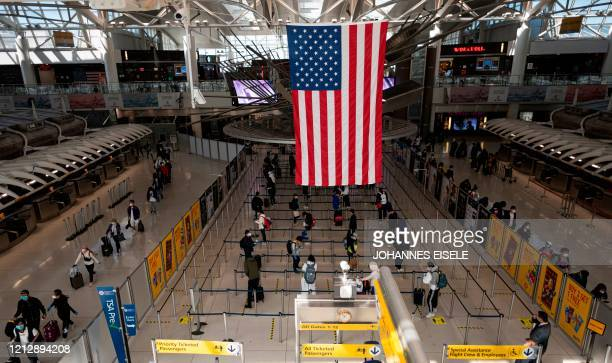 Passengers, some wearing masks and protective gear, queue for their flight at Terminal 1 of John F. Kennedy Airport amid the novel coronavirus...