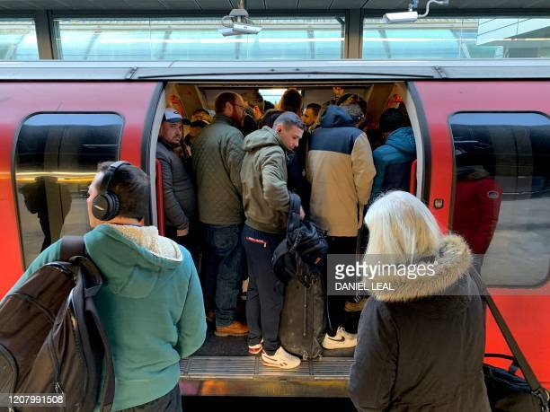 TOPSHOT Passengers squeeze on to a busy Central Line underground train at Stratford station east London March 23 2020 Amid the coronvirus pandemic...