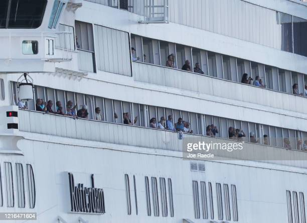 Passengers stand aboard the Rotterdam cruise ship as it arrives at Port Everglades on April 02 2020 in Fort Lauderdale Florida The Holland America...