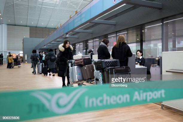 Passengers stand at a Korean Air Lines Co checkin counter inside the terminal 2 building at Incheon International Airport in Incheon South Korea on...