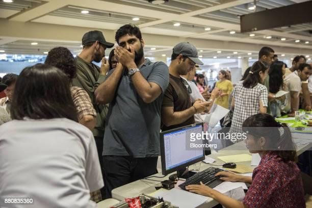 Passengers stand at a ticketing counter at Ngurah Rai International Airport near Denpasar Bali Indonesia on Tuesday Nov 28 2017 The airport...