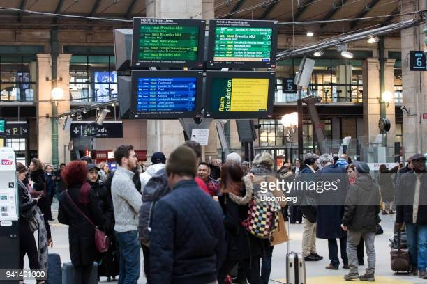 Passengers stand beneath train departure and arrival information screens on the concourse during industrial strike action by railway workers and...