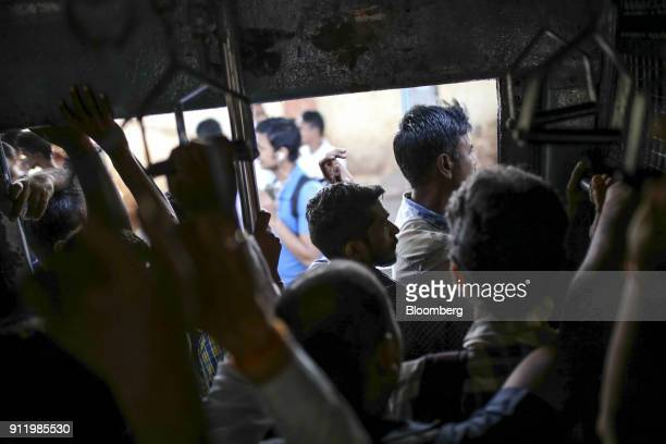 Passengers stand in a doorway of a train carriage as they travel by rail in Mumbai India on Saturday Jan 27 2018 Mumbai's suburban railway the oldest...