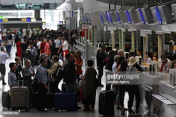 Passengers stand in line in a terminal at the airport as pilots of Lufthansa go on a 15 hours on a strike in Frankfurt Germany on September 30 2014 A...