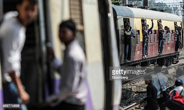 Passengers stand in the doorways of a train carriage as it arrives at Kurla railway station in Mumbai India on Wednesday April 15 2015 India's...