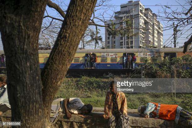 Passengers stand in the doorways of a train carriage as they travel by rail in Mumbai India on Saturday Jan 27 2018 Mumbai's suburban railway the...